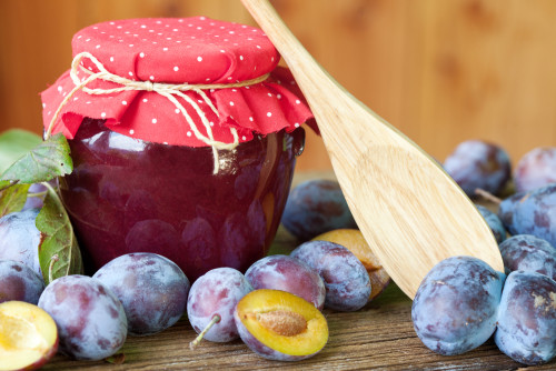 Plum jam with fresh fruits on wooden background
